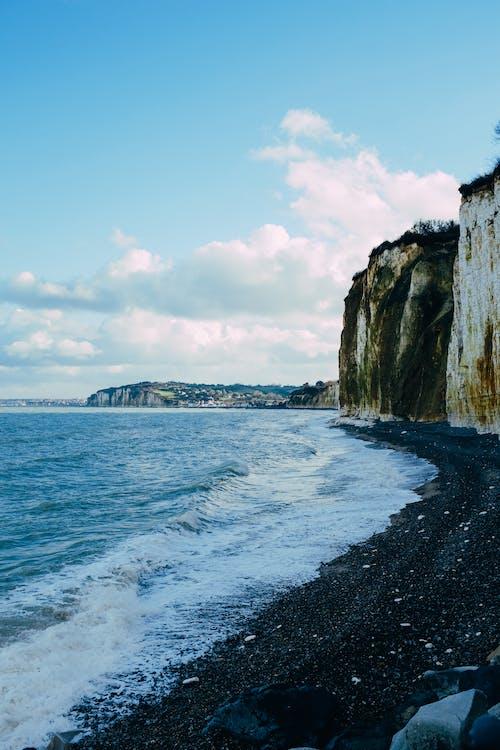 Rocky cliff washed by foamy sea