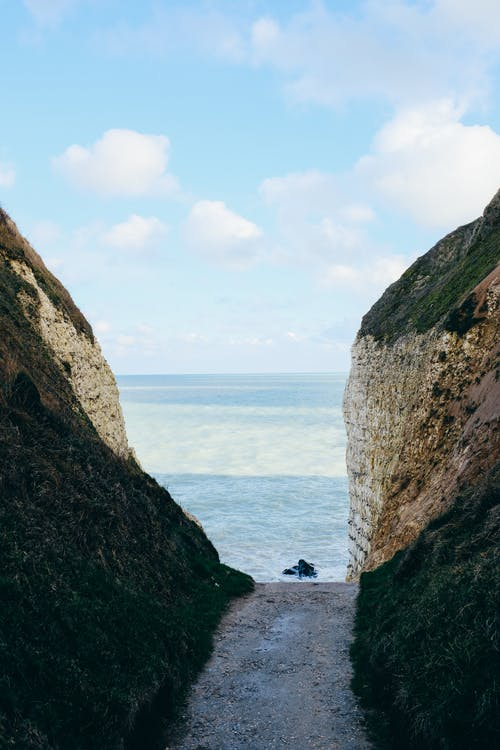 Scenic view of rough rocky cliffs forming ravine washed by foamy waving sea under clear blue sky