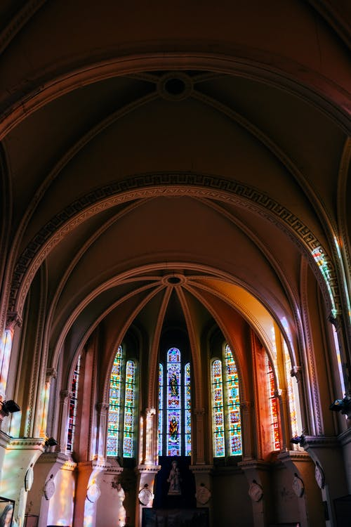 Interior design of historic cathedral dome with arched ceiling and leaded glass windows in sunlight