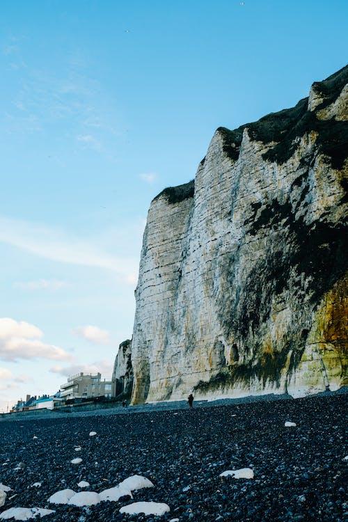 Rocky massive cliff near gravel beach