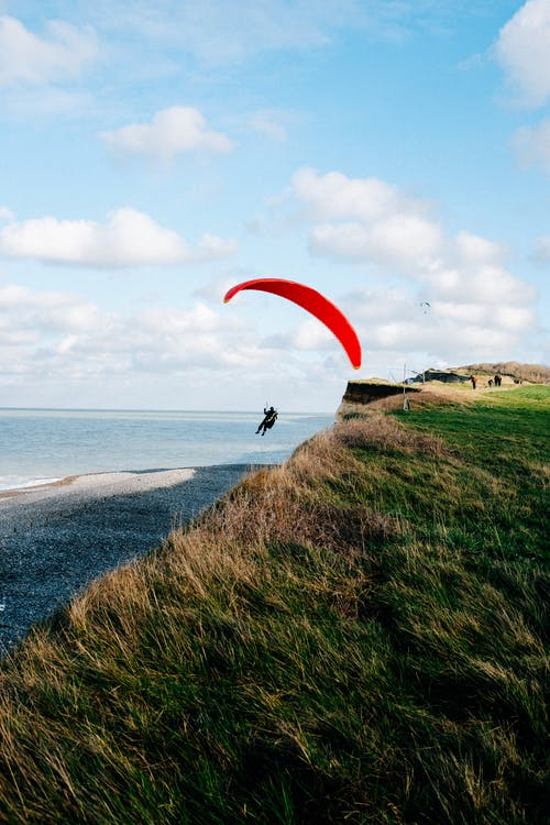 Unrecognizable paraglider flying over grassy seacoast