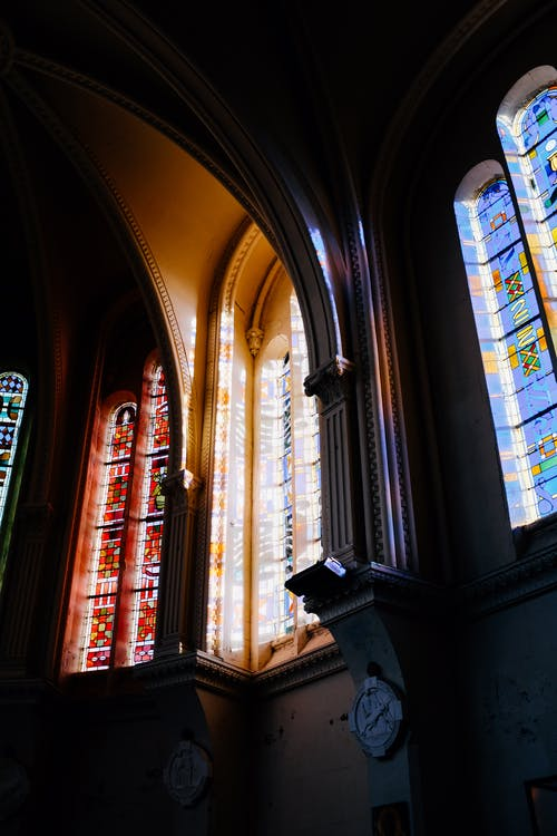 Interior design of historic cathedral dome with colorful leaded glass windows in sunlight