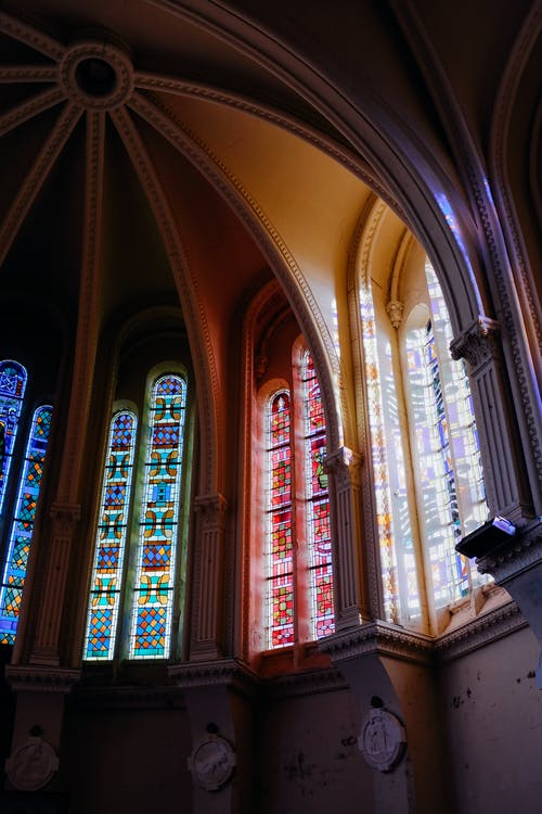 Low angle historic church dome with colorful leaded glass windows under arched ceiling in sunlight