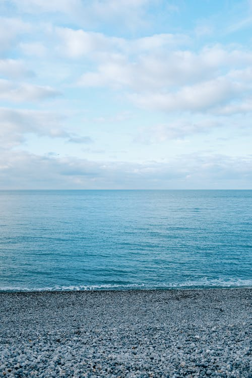 Picturesque scenery of vast peaceful blue sea under endless cloudy tranquil sky in daytime