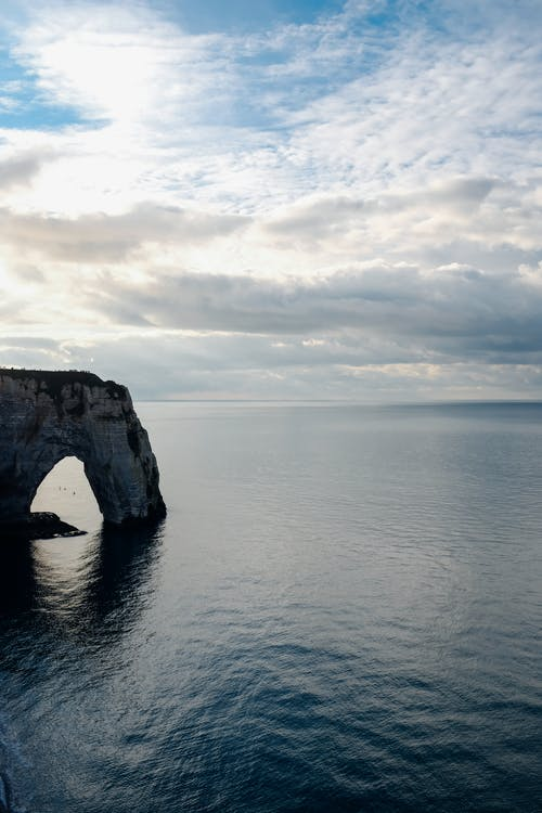 Rocky formation among calm rippling water of vast ocean