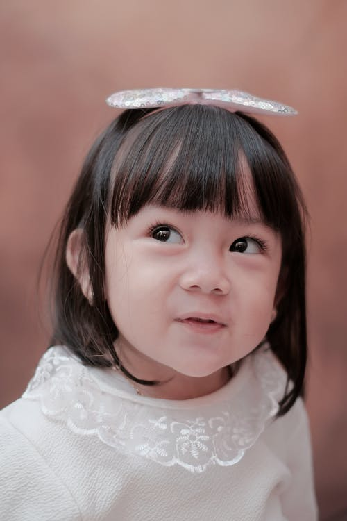 Adorable little Asian girl with dark hair in elegant clothes and headband looking away with curiosity against brown background