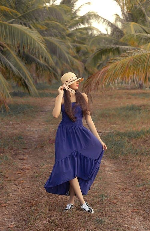Woman in Blue Dress Wearing White Sun Hat Standing on Green Grass Field