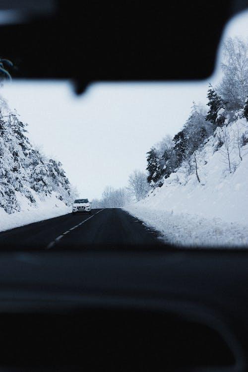 Car driving on road through snowy mountainous terrain