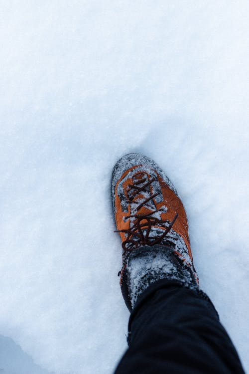 From above of crop unrecognizable traveler in boot standing on snowy terrain on winter day