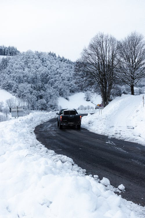 Modern automobile driving on road surrounded with leafless trees covered with snow on winter day