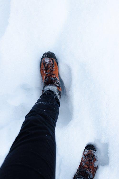 Crop person walking on snowy ground