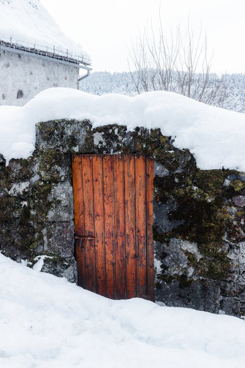 Small weathered stone shack with wooden door located on snowy terrain in rural area in countryside in cold winter day
