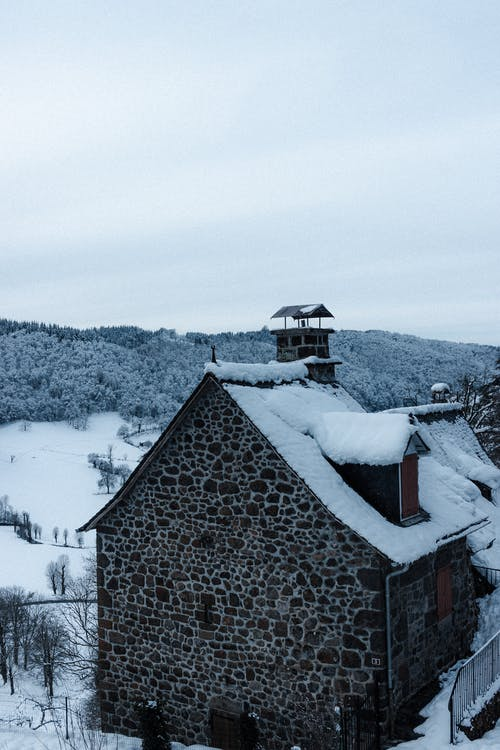Aged masonry building exterior with snow on roof against trees under cloudy sky in winter