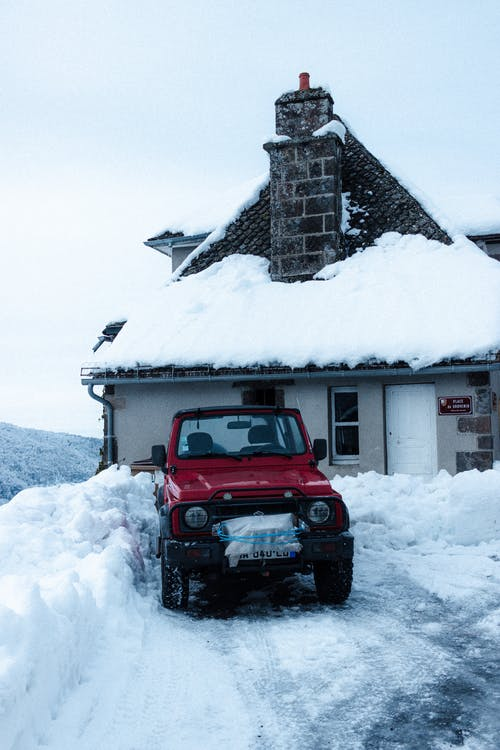 Contemporary all terrain vehicle parked against aged building exterior with snow on roof in countryside