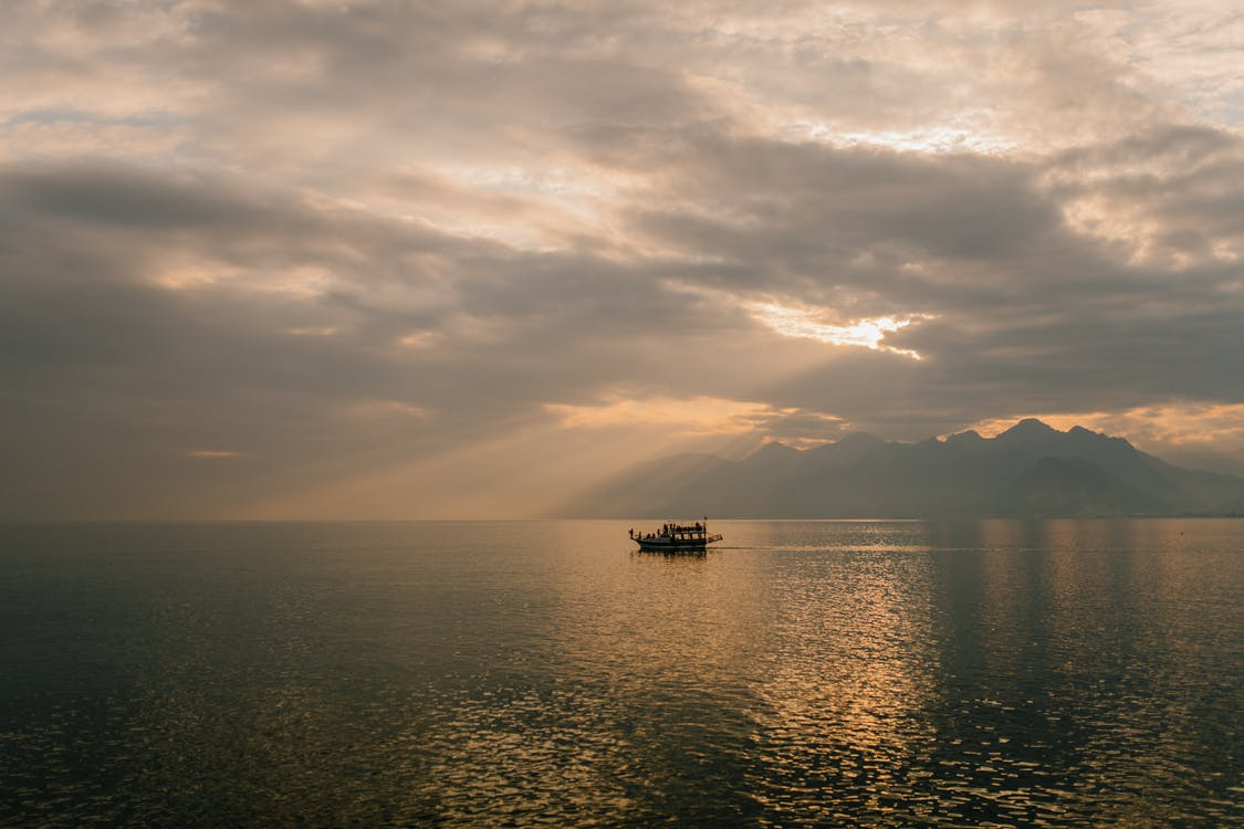 Picturesque scenery of boat floating on rippling water of sea against amazing cloudy sunset sky