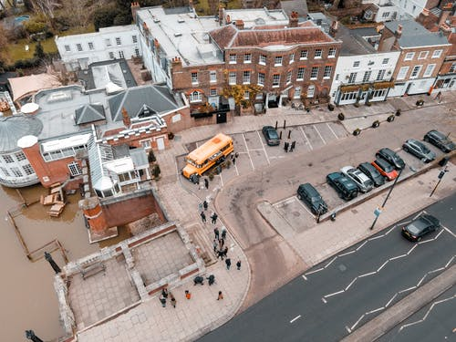 Drone view of school building facade near asphalt roadway and parking area with cars and bus with  sidewalk and people near river in city street in daytime