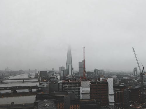 Aerial view of London city located in England with bridges over River Thames near modern buildings and Shard skyscraper under gray cloudy sky in foggy weather in daylight