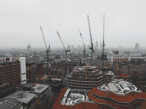 Drone view of city with buildings under construction in street under gray cloudy sky in misty weather