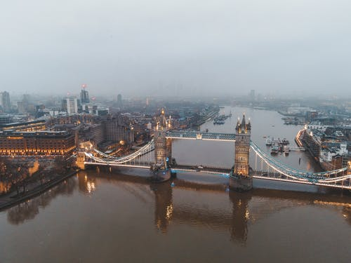 Drone view of London city located in England with illuminated Tower Bridge on River Thames near buildings in misty weather under gray cloudy sky in daylight