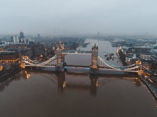 Aerial view of London city located in England with illuminated Tower Bridge on River Thames near modern buildings under gray cloudy sky in foggy day