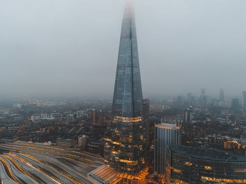 Aerial view of London city located in England with modern buildings and Shard skyscraper near railroads under gray cloudy sky in hazy day in daytime