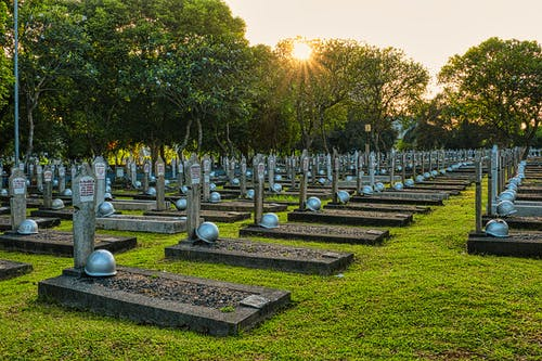 Rows of tombstones with military helmets located on grassy ground near tall lush green trees in heroes cemetery in Kalibata