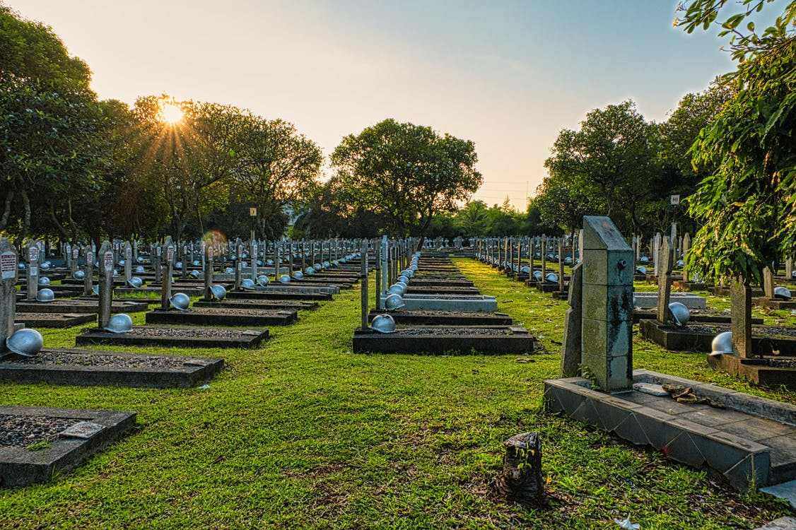 National main heroes cemetery with abundance of tombstones with military hardhats located in national cemetery with green trees in Kalibata
