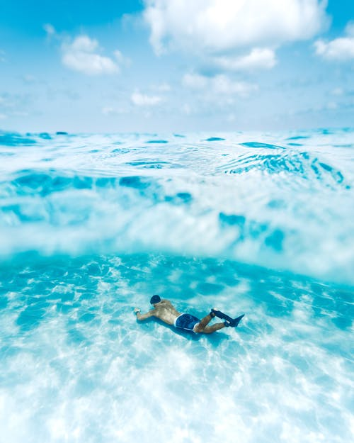 Full body of anonymous male diver with slippers swimming under transparent blue water with sun glares in tropical lagoon against cloudy sky
