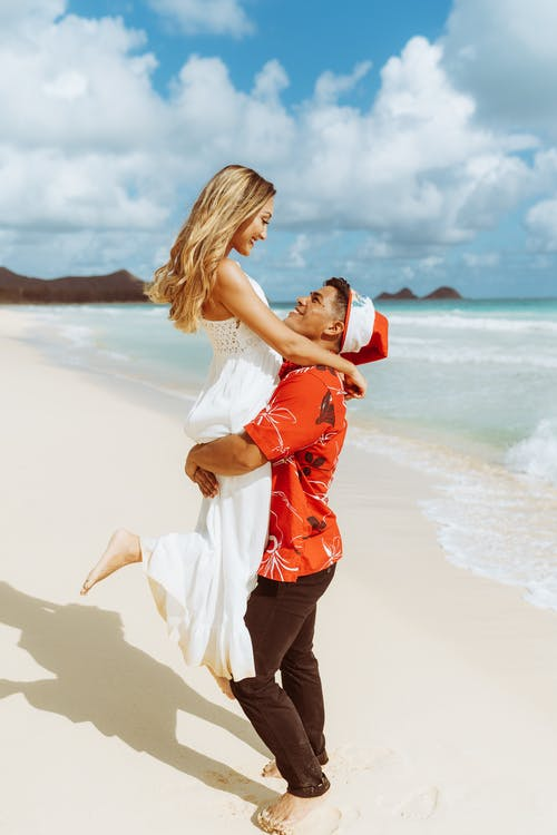 Full body side view of romantic African American boyfriend lifting barefoot girlfriend while standing on sandy shore and looking at each other near rippling sea in tropical resort
