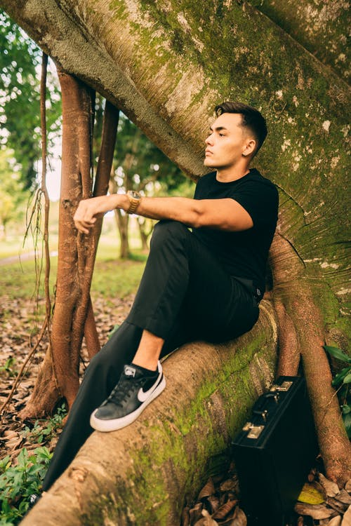 Side view of dreamy Asian male in black outfit sitting with bent leg on tree trunk covered with moss and looking into distance thoughtfully while resting in forest