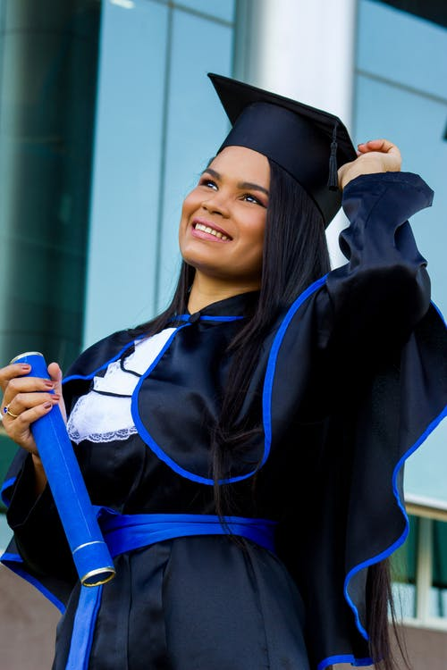 Cheerful Latin American woman in graduation outfit