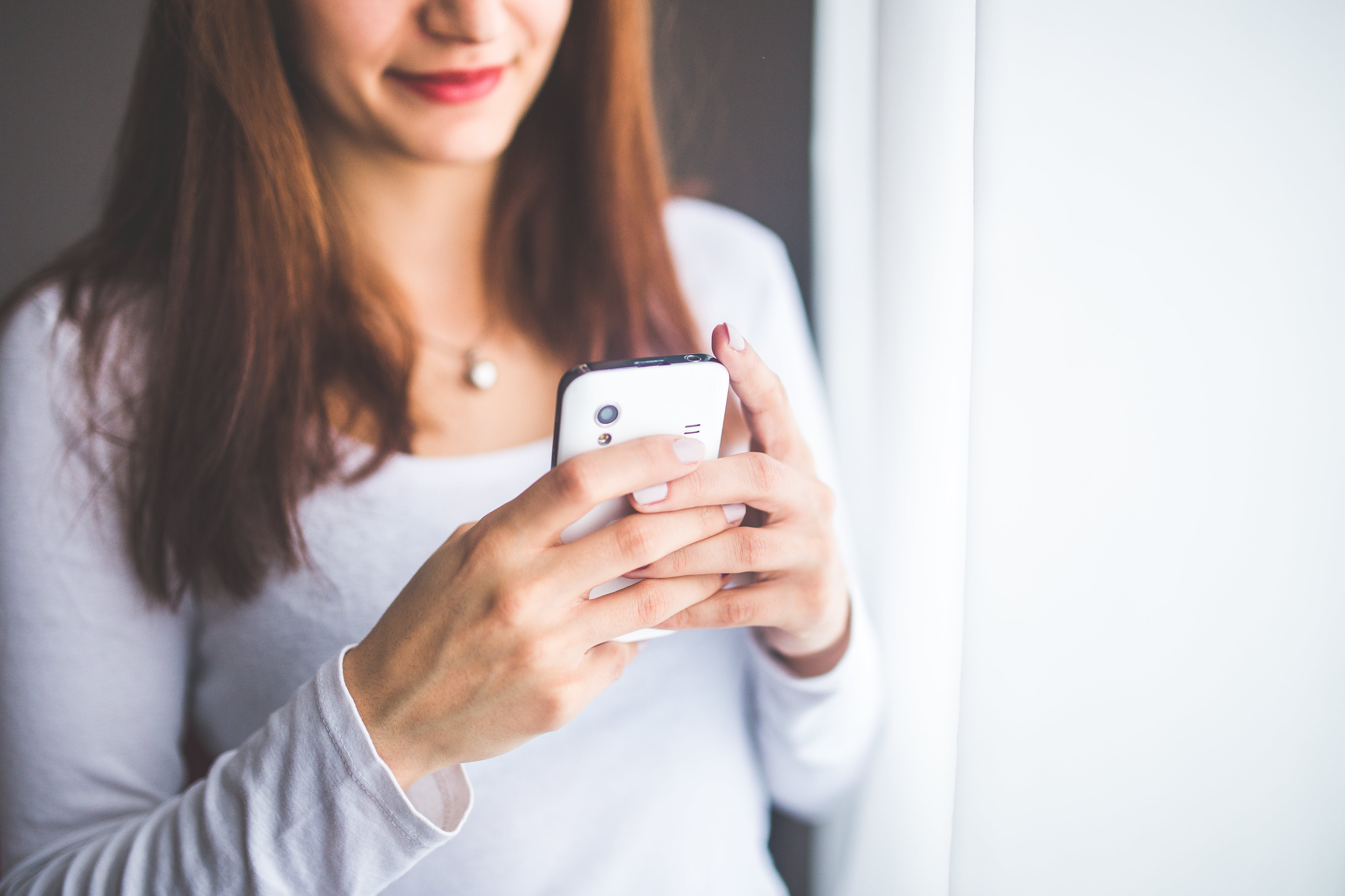 Close up portrait of a young woman typing a text message on mobile phone
