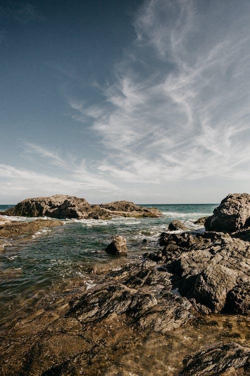 Rocks on sea coast under cloudy sky