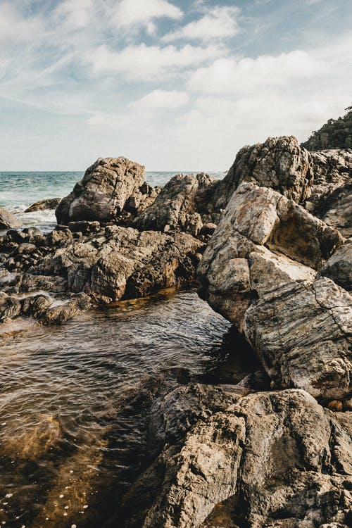Scenery view of rough dry rocky formations on shore between rippled sea in daytime