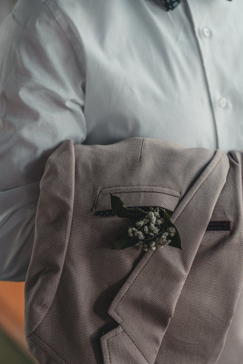 Crop unrecognizable groom holding classy jacket on hand