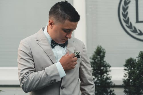 Positive ethnic groom wearing classy light tuxedo and adjusting boutonniere on pocket while standing in modern wedding hall