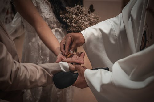 Crop faceless priest putting wedding coin on newlywed couple hands