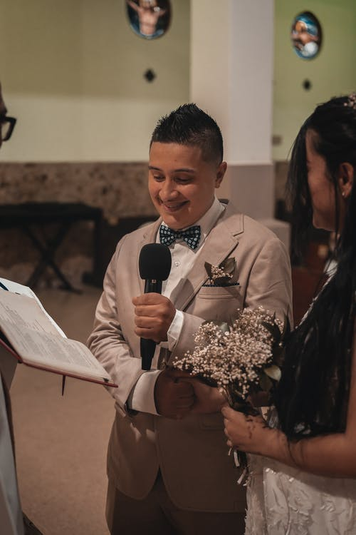 Smiling young ethnic groom in elegant suit making vow to bride during wedding ceremony in church