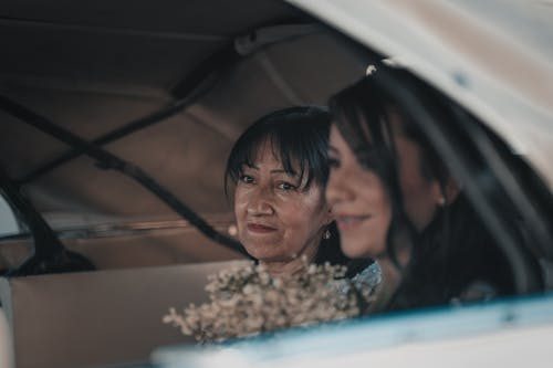 Content bride and mother sitting in car