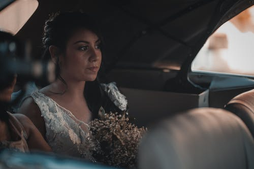 Young attractive wearing classy white dress sitting in car back seat with tender bouquet and looking away dreamily