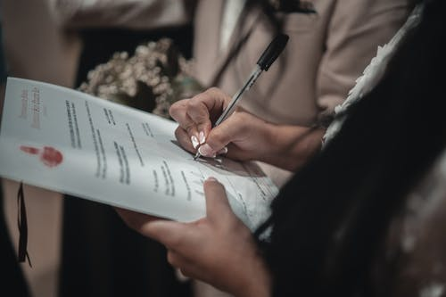 Crop unrecognizable bride signing papers in wedding hall