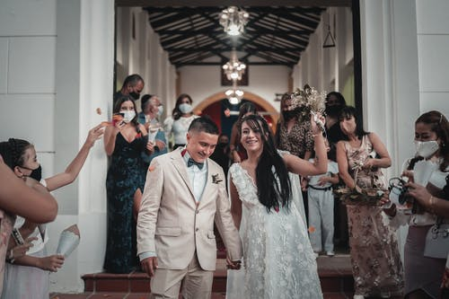 Cheerful ethnic newlyweds leaving church after ceremony