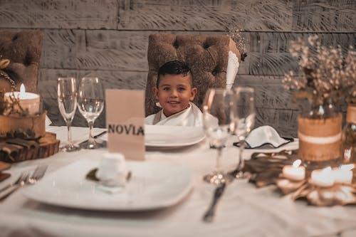 Little cute ethnic boy at festive table on wedding