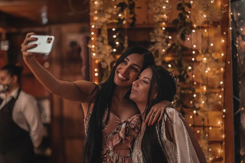 Happy ethnic woman hugging girlfriend and taking selfie on smartphone