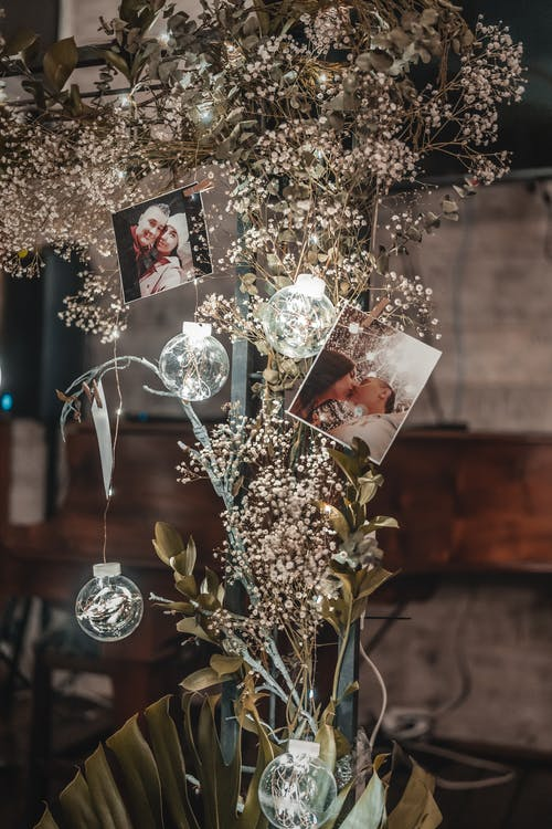Floral composition with decorative shiny garland and glass balls and photos of couple at event
