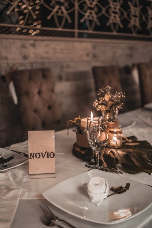 High angle of elegant tableware placed with napkins and burning candles on table for event