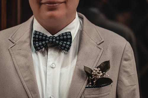 Crop fiance in elegant suit with bow tie and boutonniere for wedding ceremony