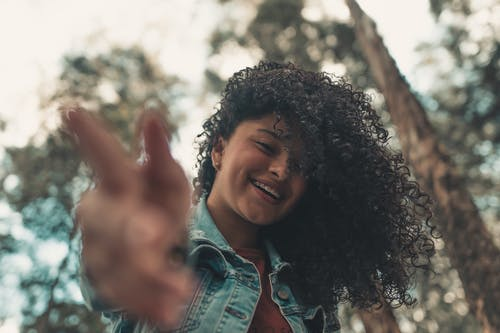 Low angle of delighted African American teen woman with curly hair and braces standing against blurred trees in forest