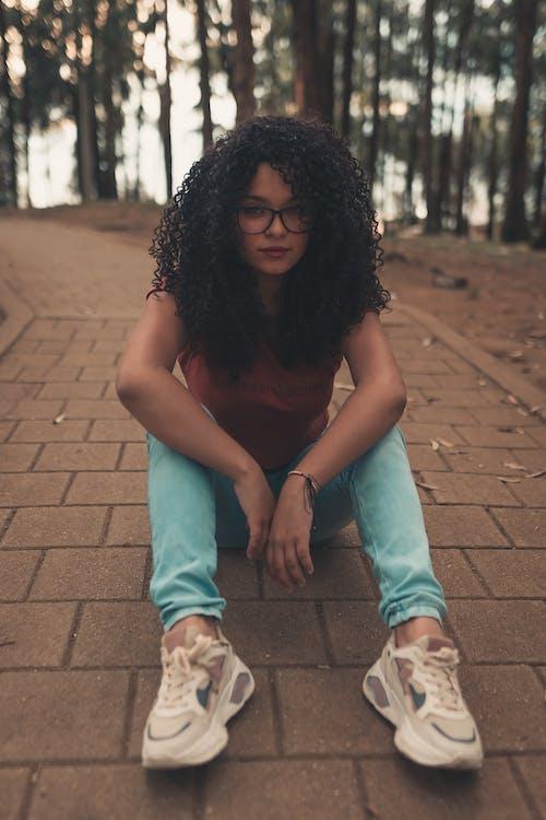 Black teenager sitting on footpath among trees