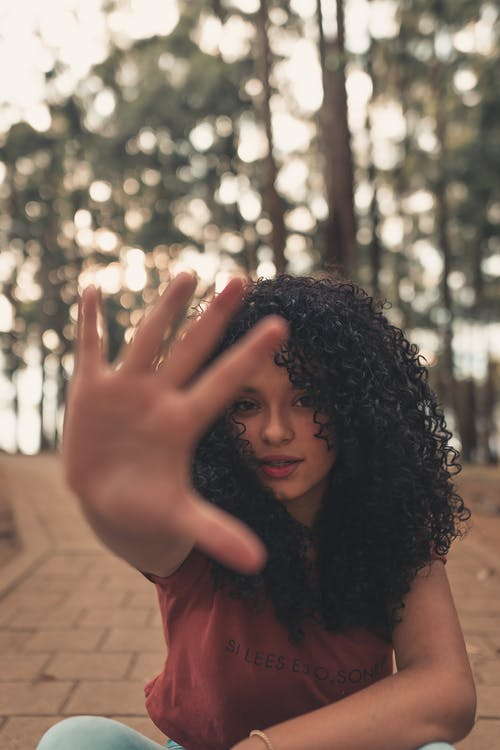Calm ethnic female with black curly hair reaching hand to camera while sitting on paved walkway against green trees on blurred background